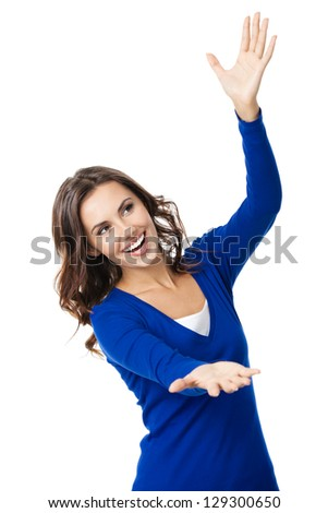 Happy smiling beautiful young woman carring, holding or showing something transparent or visual imaginary, isolated over white background