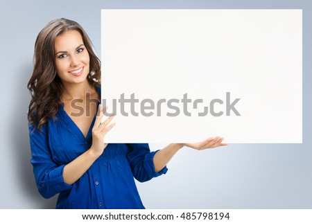 Happy smiling beautiful young woman showing blank signboard or copyspace
