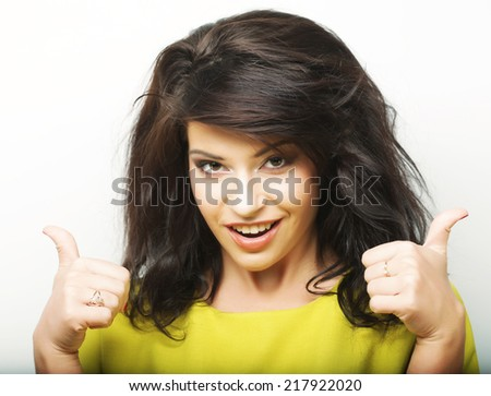 Happy smiling beautiful young woman showing thumbs up gesture  - stock photo