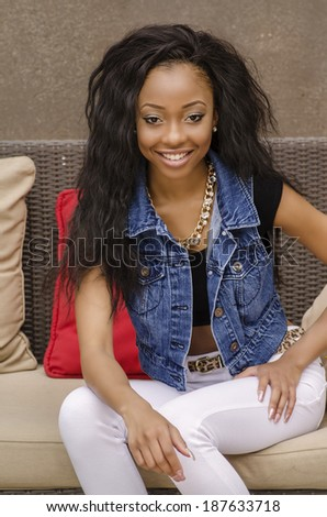 Happy smiling beautiful young woman wearing white denim jeans and top. - stock photo