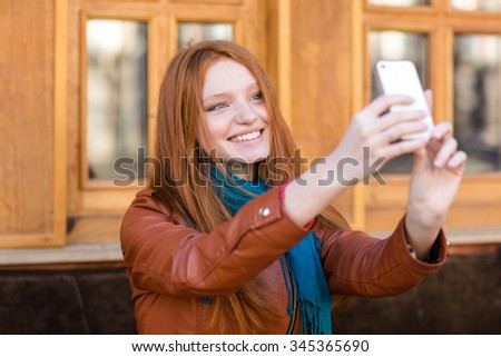 Happy smiling beautiful young woman with long red hair in leather jacket and scarf making selfie in outdoor cafe