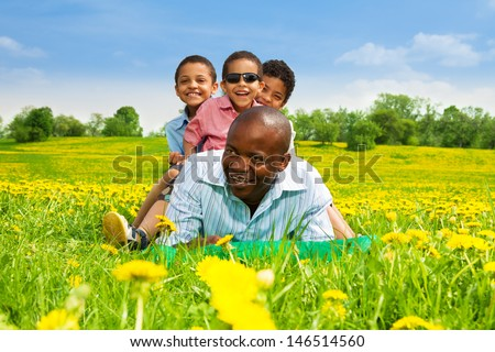 Happy smiling black African man with boys sitting on his back laying in the spring park field with yellow dandelions