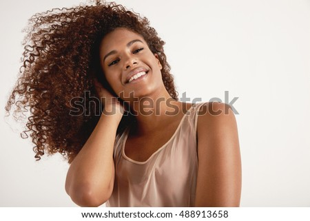 happy smiling black woman with curly hair wears delicate dress