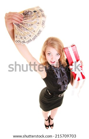 Happy smiling blond girl young woman in black dress holding big red christmas gift box with ribbon and polish currency money banknote. Holidays time for gifts.