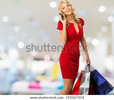 Happy smiling blond woman with shopping bags and mobile phone in shop interior  - stock photo