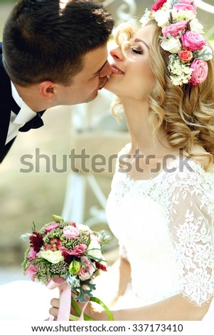 Happy smiling blonde bride in white dress and wreath kissing handsome groom