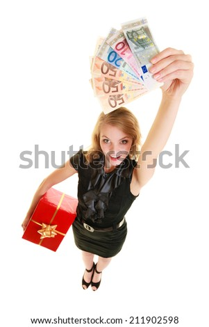 Happy smiling blonde girl young woman holding red christmas gift box and euro currency money banknotes. Holidays time for gifts. - stock photo