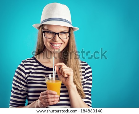 Happy smiling blonde in white hat holding glass of cocktail posing in studio. Young attractive Caucasian woman in eyeglasses thinking of summer holidays.  - stock photo