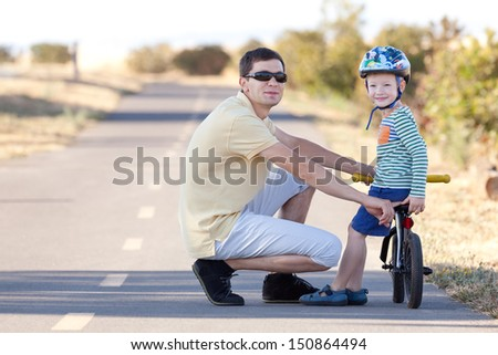 happy smiling boy at the balance bike and his handsome father walking together - stock photo