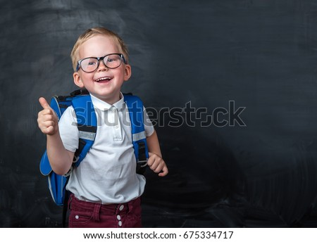 Happy smiling boy in glasses with thumb up is going to school for the first time. Child with school bag and book. Kid indoors of the class room with blackboard ona background. Back to school.