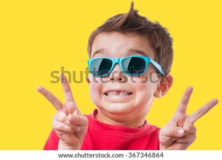 Happy smiling boy in red t-shirt and sunglasses showing peace or victory hand triumph, childhood, fashion and people concept, on yellow background - stock photo