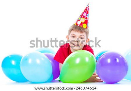 Happy smiling boy in red t-shirt lying on the floor with colorful balloons - isolated on a white. - stock photo