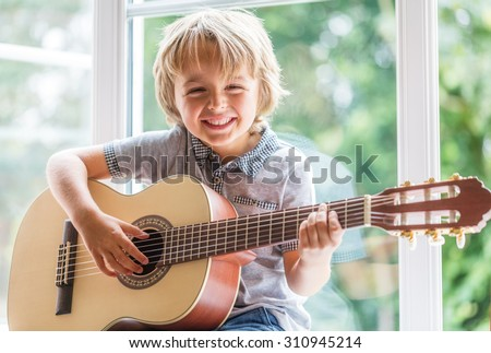 Happy smiling boy learning to play the acoustic guitar - stock photo