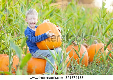 happy smiling boy sitting with huge pumpkin and enjoying fall festival and pumpkin patch, american tradition - stock photo