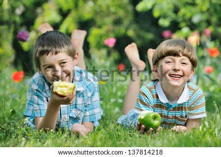 Happy smiling boys eat apple on a grass outdoors in spring park - stock photo