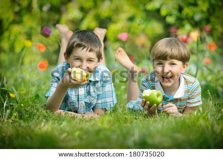 Happy smiling boys eat apple on a grass outdoors in spring park