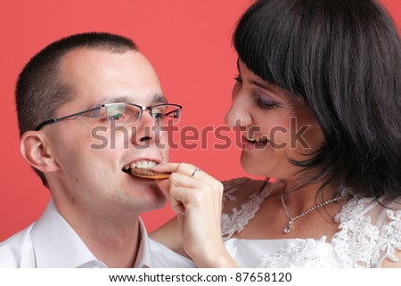 Happy smiling bride and groom young happy couple playfully eating cake on red background