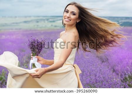 Happy smiling bride at purple lavender field - stock photo