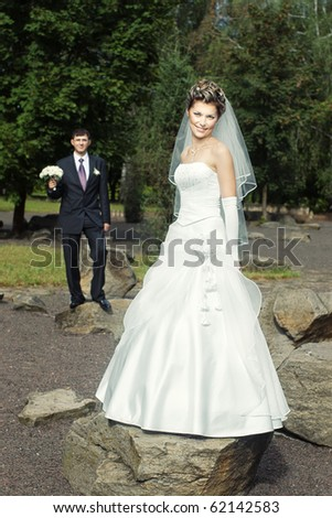 Happy smiling bride standing on a rock outdoors with blurred groom in the background