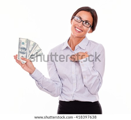 Happy smiling brunette businesswoman holding dollar bills while smiling and looking away, marveling with one hand on her chest in a button down shirt and her hair tied back on a white background