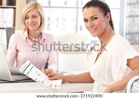 Happy smiling, brunette casual businesswoman working at office with business report in hand, looking at camera. - stock photo
