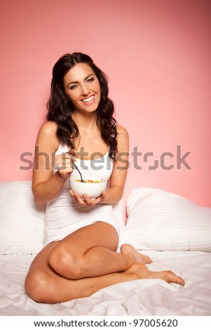 Happy smiling brunette woman having a bowl of breakfast cereal curled up on her bed - stock photo