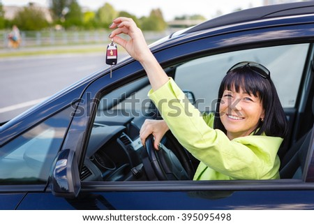 Happy smiling brunette woman Showing Car Key sitting in car with spring-summer mood. Dressed in green jacket with sun glasses on head. Woman Driving - stock photo