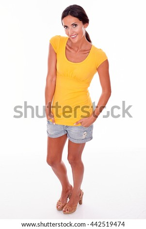 Happy smiling brunette woman with her hands in her pockets while looking at camera and wearing a yellow t-shirt and short jeans isolated