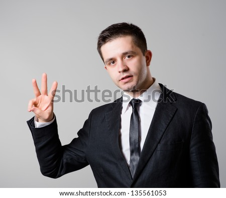 Happy smiling business man showing three  fingers