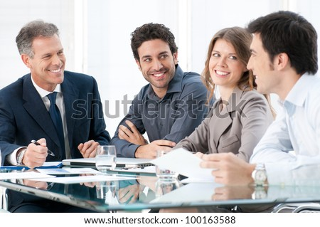 Happy smiling business people discussing and working together at office - stock photo