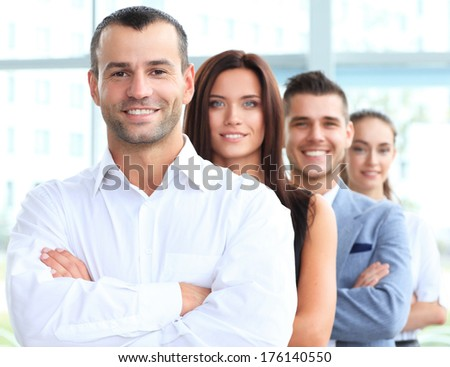 Happy smiling business team standing in a row at office  - stock photo