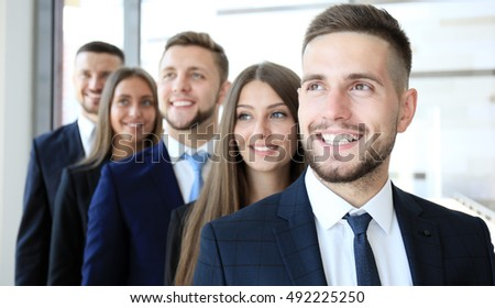 Happy smiling business team standing in a row at office