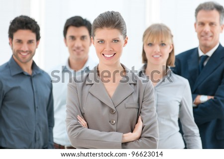 Happy smiling business woman looking at camera with her colleagues at office - stock photo