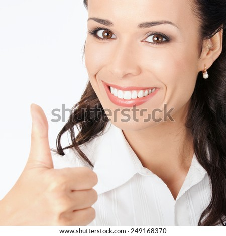 Happy smiling business woman showing thumbs up gesture, against grey background