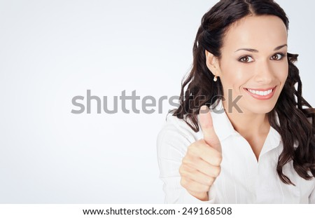 Happy smiling business woman showing thumbs up gesture, against grey background, with copyspace