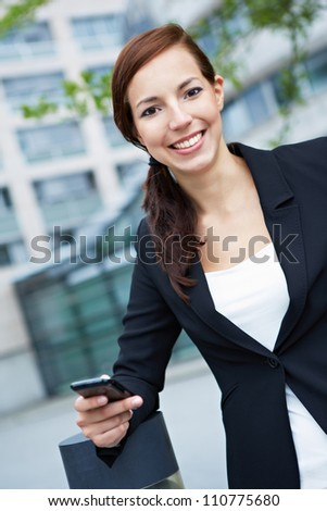 Happy smiling business woman with a smartphone in the city - stock photo