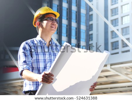 Happy smiling businessman holding blueprint for new project while working at constructions site.
