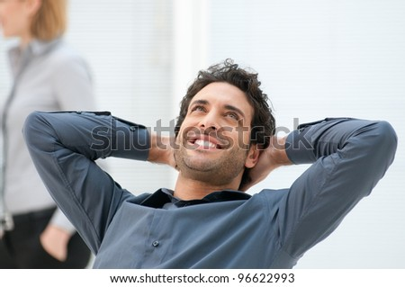 Happy smiling businessman looking up with dreaming expression at office