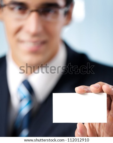Happy smiling businessman showing blank business card, at office. Focus on hand.