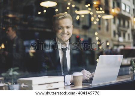 Happy smiling businessman wearing black suit and using modern laptop while sitting in coffee shop interior, successful employer working on notebook computer in cafe on a break, film effect - stock photo