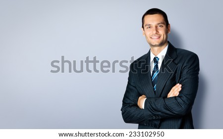 Happy smiling businessman with crossed arms pose, with blank copyspace area for text or slogan, against grey background - stock photo