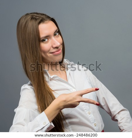 Happy smiling businessman with thumbs up gesture, on grey background