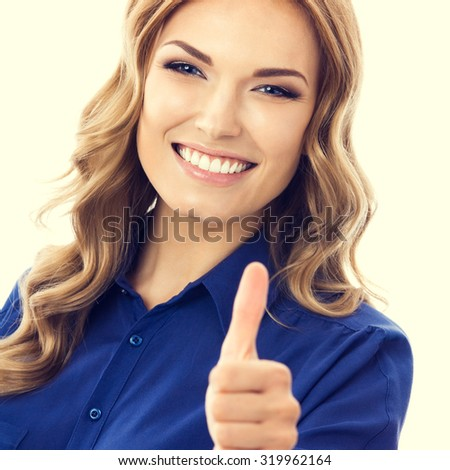 Happy smiling businesswoman in blue clothing showing thumbs up hand sign gesture - stock photo