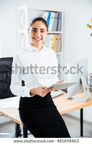 Happy smiling businesswoman leaning on the office desk and using pc tablet, looking at camera