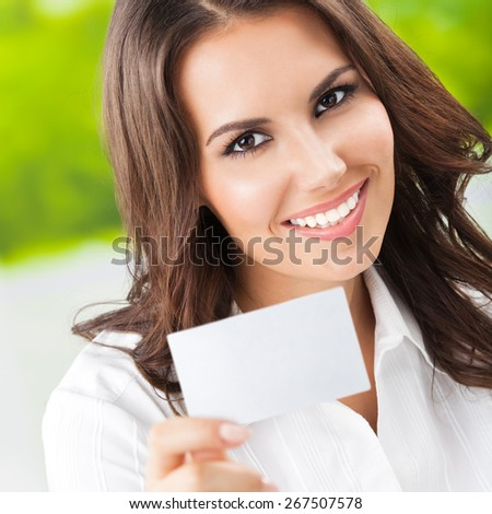 Happy smiling businesswoman showing blank business or plastic card with copyspace area for slogan or text. Invitation concept. - stock photo