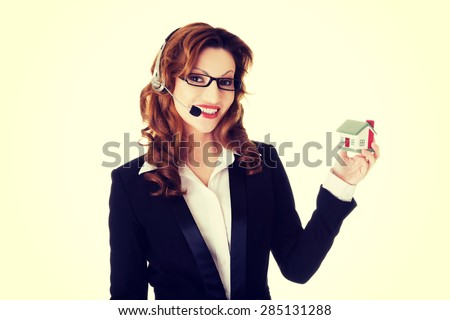 Happy smiling call center woman showing house model. - stock photo