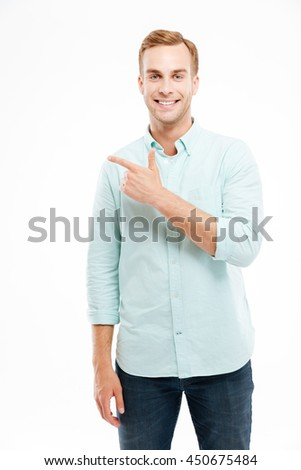 Happy smiling casual man pointing finger away at copyspace isolated on a white background - stock photo