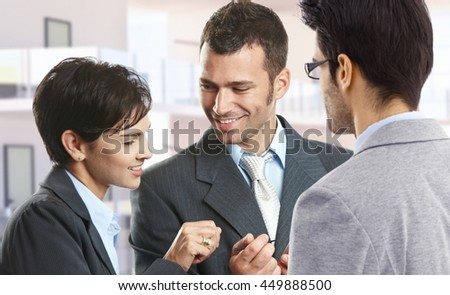 Happy smiling caucasian business people at office hall. - stock photo