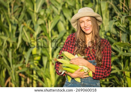 Happy smiling caucasian female farmer or gardener in a hat holding corn, fresh vegetables. Agriculture - food production, harvest concept - stock photo