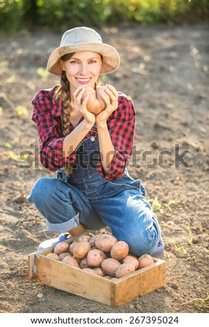 Happy smiling caucasian female farmer or gardener in a hat holding potato, fresh vegetables. Agriculture - food production, harvest concept, focus on face - stock photo